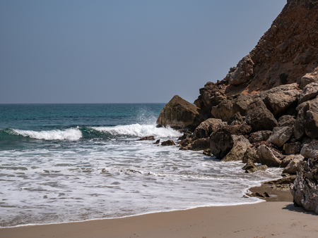 Closer shot of a Lonely and deserted beach with an outcropping of rocks in the distance