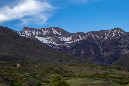 Beautiful landscape of snow on the mountains with a clear sky and some clouds