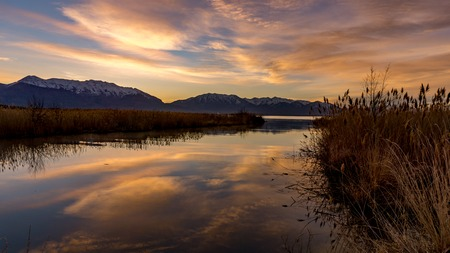 Golden morning sunrise colors reflecting off the lake with the snow-capped Rocky Mountains in the background Stok Fotoğraf