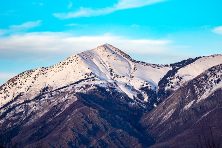 Majestic snow-capped mountain and ridgeline with some clouds inthe sky