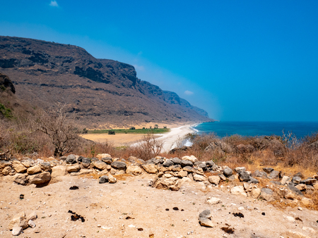 Deserted and lonely ocean and beach with mountains in the distance near Salalah, Oman