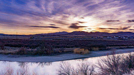 Beautiful Magenta sunset beyond the Rocky Mountains with a reflective river in the foreground Stok Fotoğraf