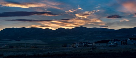 Nighttime shot of housing construction against a colorful sunset and the rocky mountains