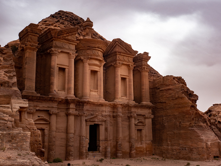 Sunlight breaks through the clouds and lights up the front of the Monestary at Petra Jordan