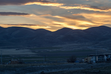 Golden sunset and mountains in the background of housing construction in the foreground