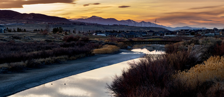 View of wind turbines and a river with a bridge crossing in the foothills at sunset Stok Fotoğraf