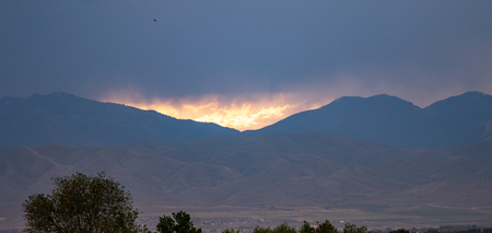 Fire-like sunset between the peaks of the Rocky Mountains on a hazy day Stok Fotoğraf