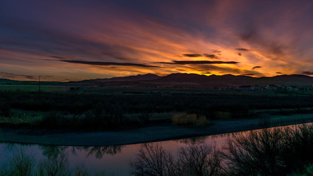 Stunning golden colors light the sky and reflect off the river at sunset in this colorful panorama Stok Fotoğraf