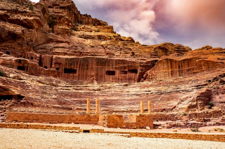 Ruins of the ancient Roman theater carved into the sandstone with a dramatic sky overhead