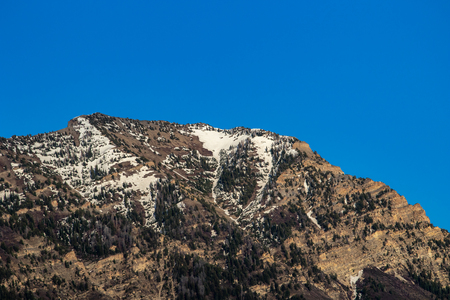 Clear blue sky above the snow-capped peak of a mountain