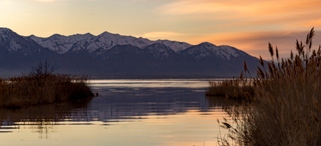 Panorama view of a reflective lake with mountains in the background during the golden hour