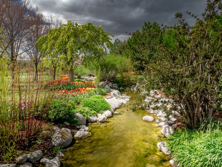 Small stream flowing through a park with flowers and trees all around