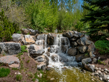 Small waterfall flowing through a park with flowers and trees all around Stok Fotoğraf