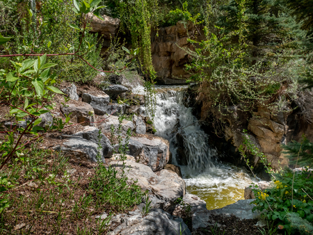 Small waterfall flows and splashes along a mountain stream Stok Fotoğraf