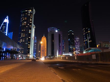 Late night streets against the bright lights of Doha, Qatars modern landmarks