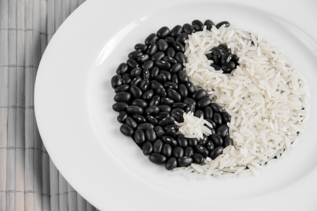 Yin Yang symbol made with white rice and black beans. photo