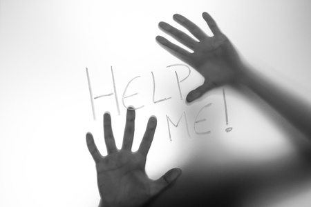 Help me written on a glass with a human figure behind and touching with the hands.
