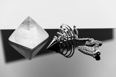 esoterismo: Péndulo de metal para radiestesia y un claro pirámide de cuarzo. Foto de archivo