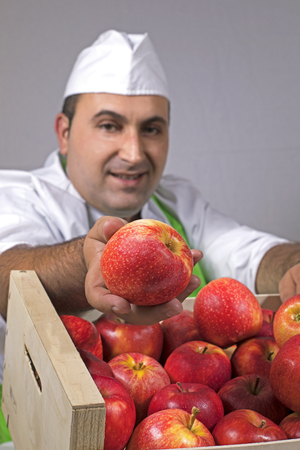 Fruit seller offering a red apple from a box. Banco de Imagens