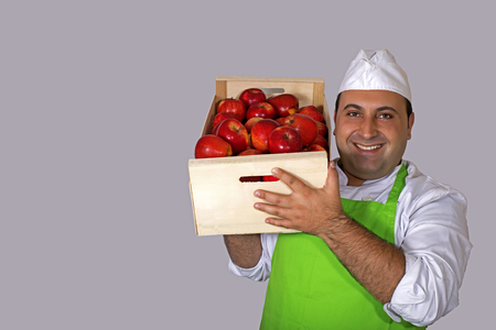 Fruit seller carrying a box of red apples on his shoulder.