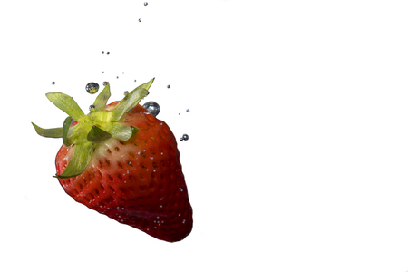 Ripe strawberry on white background submerged in water with bubbles