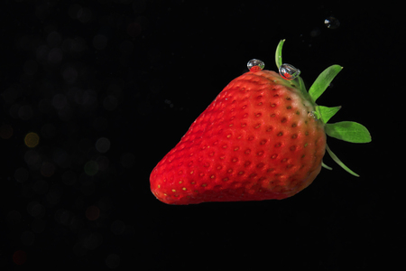 Ripe strawberry on black background submerged in water with bubbles