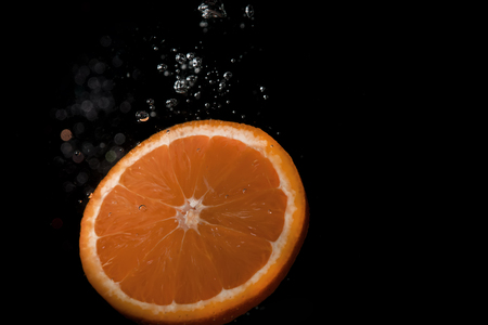 Orange slice on black background submerged in water with bubbles