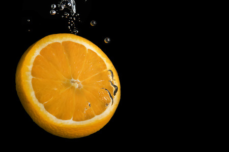 Slice of lemon on black background submerged in water with bubbles