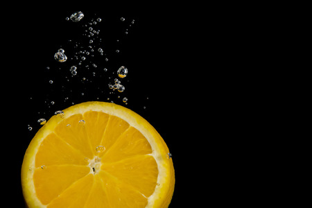 Lemon slice on black background submerged in water with bubbles