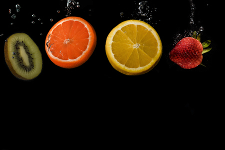 Four slices of fruit lined up, with space below to add text: Kiwi, Orange, Lemon and strawberry. Black background. 免版税图像