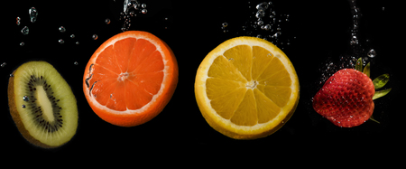 Four slices of fruit in a row: Kiwi, Orange, Lemon and strawberry. Black background. Banco de Imagens