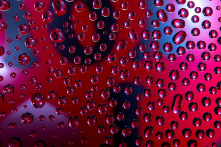 Phrase I Love You written on a red balloon reflected in drops of water