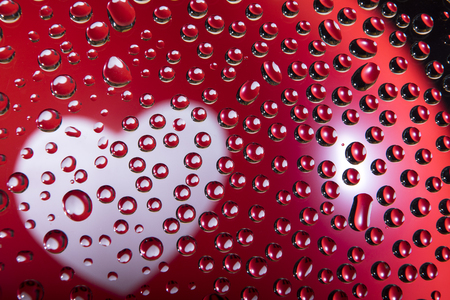 Heart of white color in a red balloon reflected in drops of water