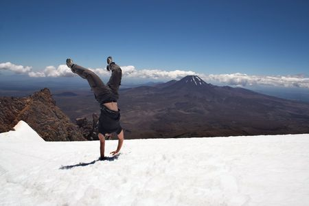 doom: Handstand on snow at Mt Ruapehu, down-under New Zealand.  Mount Ngauruhoe (Doom) is visible on the horizon. Stock Photo
