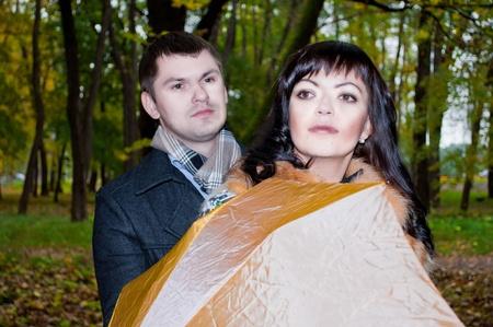 Portrait photo of happy couple in autumn with orange umbrella photo