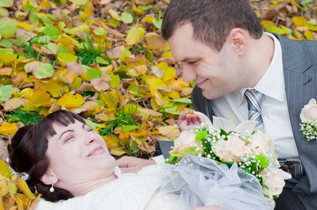 the happy newly-married couple playing in the gold autumn Stock Photo - 11510336