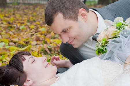 the happy newly-married couple playing in the gold autumn Stock Photo - 11510320