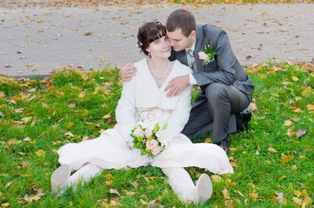 the happy newly-married couple playing in the gold autumn  photo