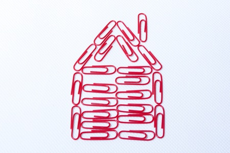 desing a house with red paper clips on the white backgraund photo