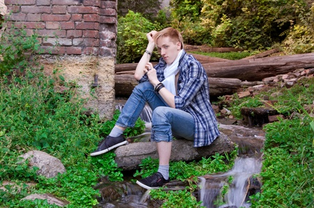 siting: Young human is siting among greenery, old logs and small beautiful waterfall Stock Photo