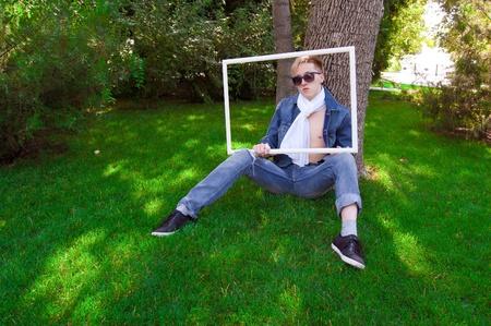 pensiveness: Umano giovane sul prato verde con cornice bianca, ha gli occhiali blu e giubbotto di jeans Archivio Fotografico