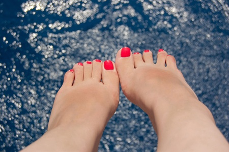foots: The beautiful legs of the woman with red manicure on background blue sea