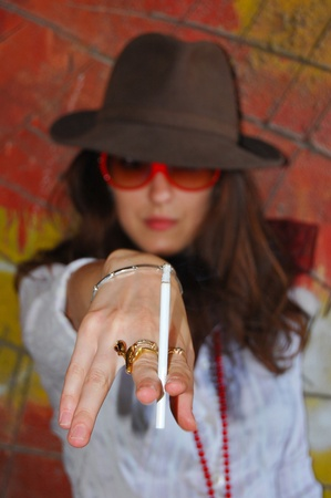 reg: young girl is standing near bright reg and yellow wall  with brown hat on her head and with cigarette in her hand