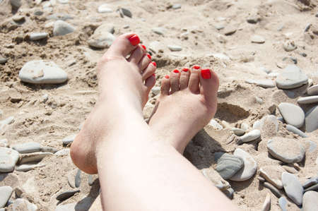 foots: Two foots and one arm with bright manicure on the background stony-sandy beach. summer