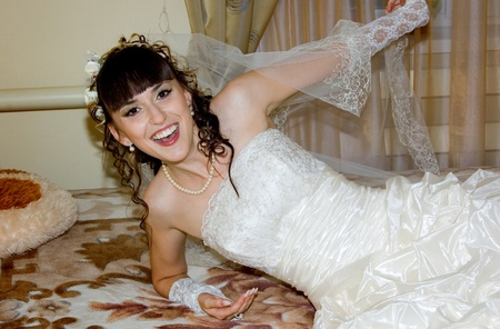 The young beautiful fiancee is play with wedding veil and she is lie on the bedstead photo