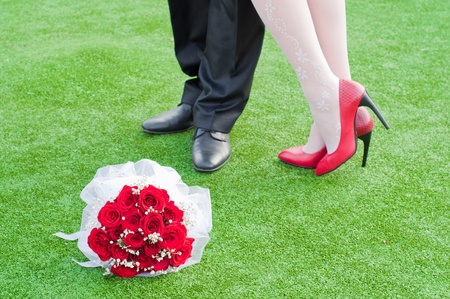 legs of bride and fiance on the green grass with wedding red bouquet  photo