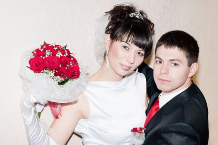 newly-married couple standing near the wall with red bouquet photo