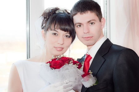 newly-married couple standing near the window with red bouquet photo