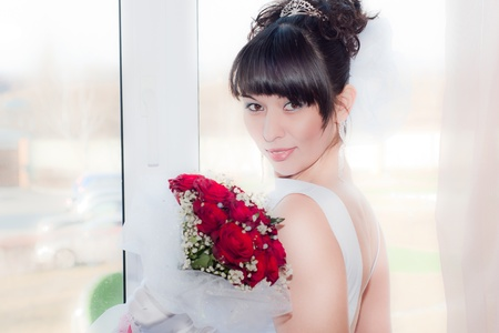 Beautiful brunet bride holding bouquet of red flowers photo