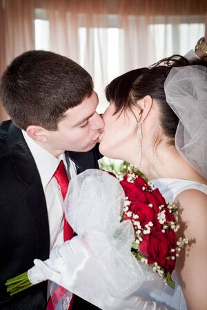 newly-married couple standing near the window and kissing photo